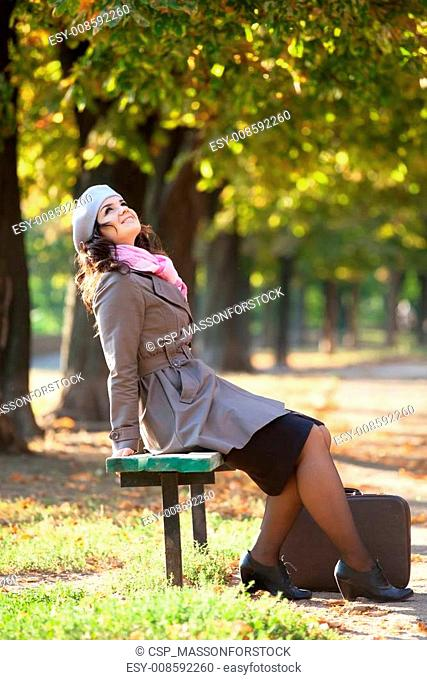 Girl with suitcase at autumn outdoor