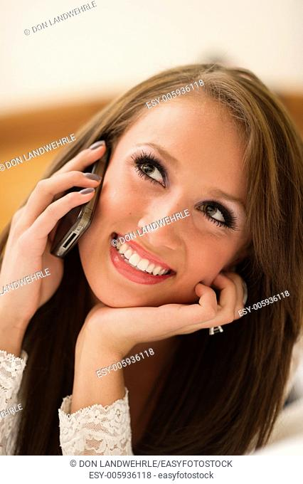 Teenage girl lying on a bed talking on a cell phone