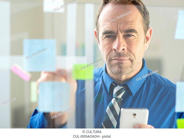 Businessman with smartphone sticking notes on office glass wall