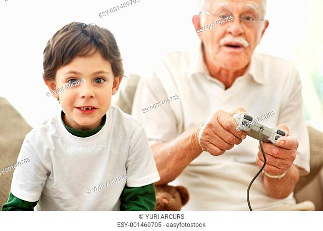Portrait of boy and his grandfather with video game controllers sitting on sofa - Indoors