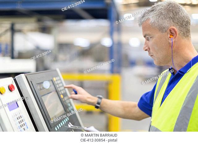 Worker operating machinery at control panel in steel factory