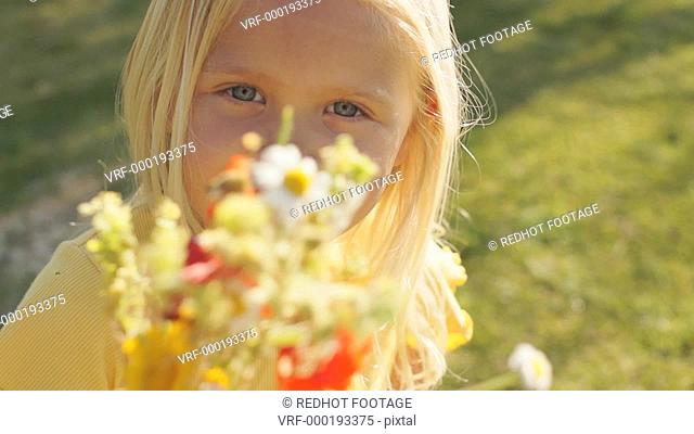 Portrait of one child with bunch of wild flowers in park