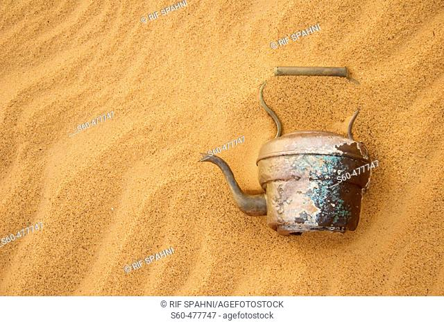 Abandoned tea pot in the Argelian desert. Hamada of Tinduf. Half covered by sand. Tinduf. Argelia
