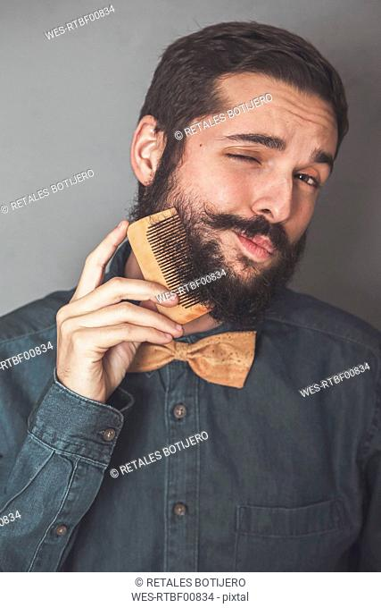 Man combing his beard with a wooden comb, wearing denim shirt and cork bow tie