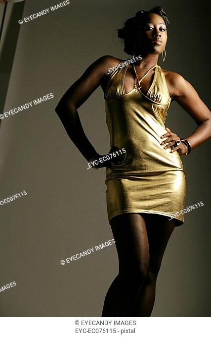 Young African American woman in gold dress, studio shot