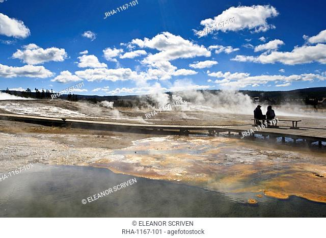 Cold tourists on seat surrounded by steam, Upper Geyser Basin, Yellowstone National Park, UNESCO World Heritage Site, Wyoming, United States of America