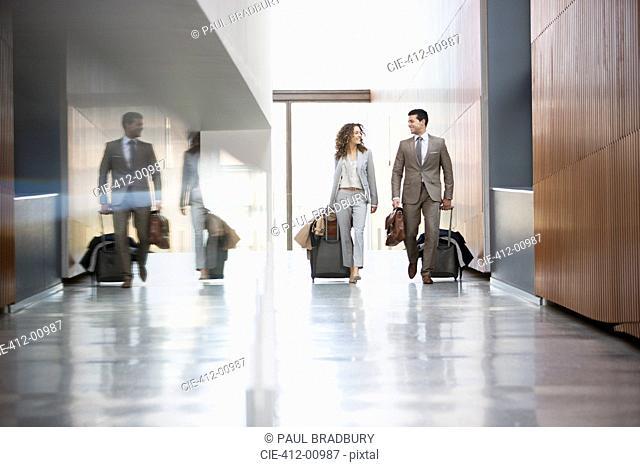 Businessman and businesswoman pulling suitcases through corridor