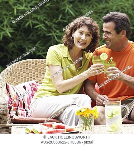 Mature couple toasting glasses of lemonade