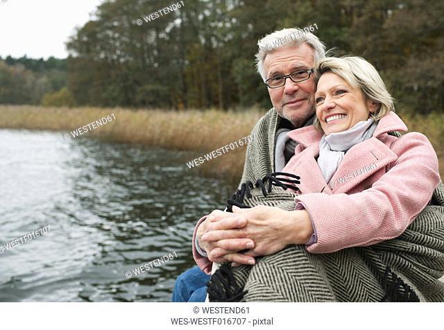 Germany, Kratzeburg, Senior couple sitting on boardwalk, smiling