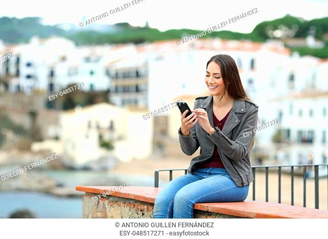 Happy woman sitting on a ledge using a smart phone in a coast town