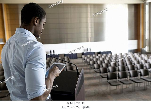 Man with digital tablet at podium in empty auditorium