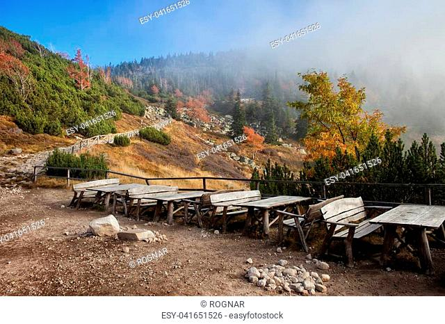 Picnic tables with benches, rest place in autumn landscape of Karkonosze Mountains, Poland