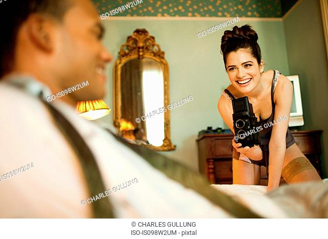 Woman photographing man in hotel room
