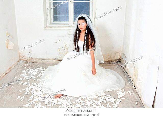 Woman in wedding gown in empty house
