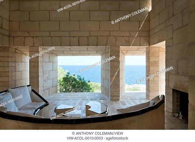 Can Lis, Mallorca, Spain. Architect: Utzon, Jorn, 1971. Living room with built in crescent shaped sandstone sofa with frameless windows and shaft of light...