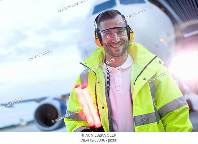 Portrait smiling air traffic controller in front of airplane on tarmac
