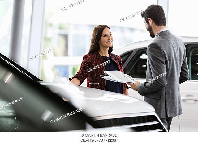 Car saleswoman showing brochure to male customer in car dealership showroom