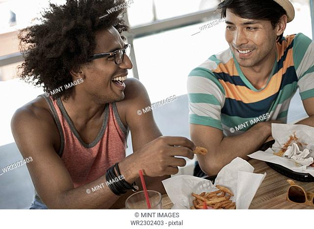 Two young men sitting eating at a diner