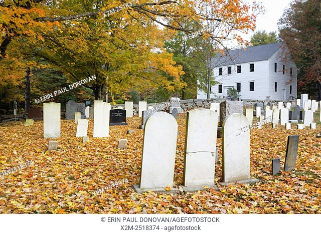 Meeting House Cemetery in Danville, New Hampshire USA during the autumn months. Hawke Meeting House is in the background