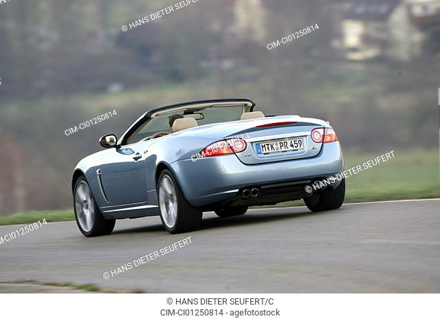 Jaguar XKR Convertible, model year 2006-, silver, driving, diagonal from the back, rear view, country road, open top