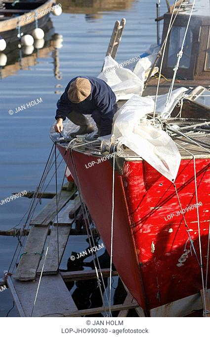Scotland, North Ayrshire, Corrie, A fisherman painting his boat in Corrie Harbour on the Isle of Arran