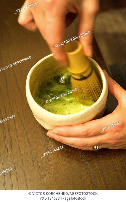 Preparation of Japanese matcha tea in a cup with a whisk