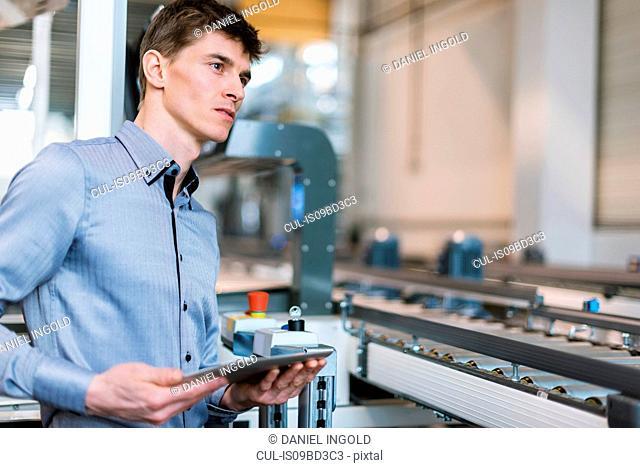 Young man in factory, beside conveyor belt, holding digital tablet