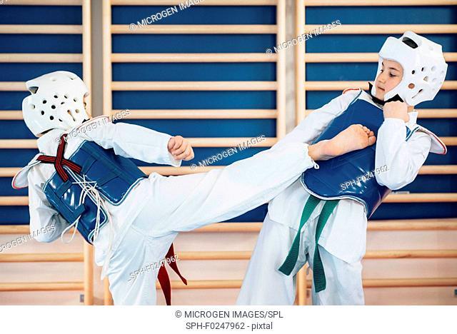 Two kids sparing in taekwondo class