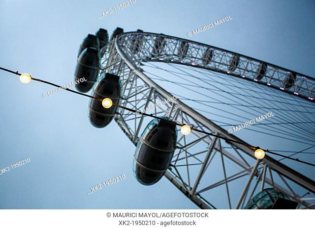 Close up of light bulbs and London Eye at dusk, London, UK