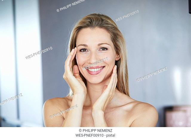 Portrait of smiling blond woman touching her face