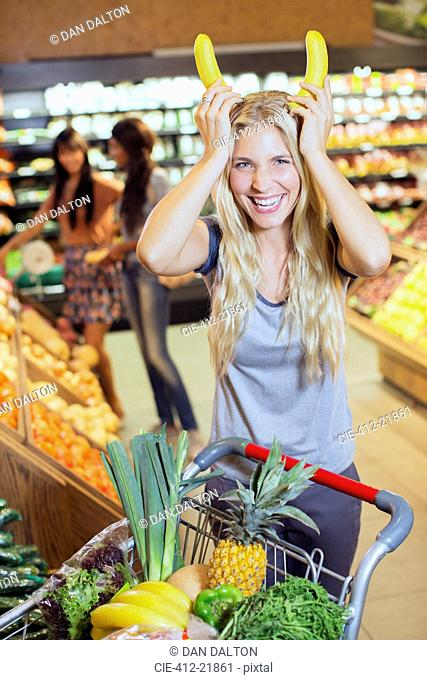 Woman playing with bananas while shopping in grocery store