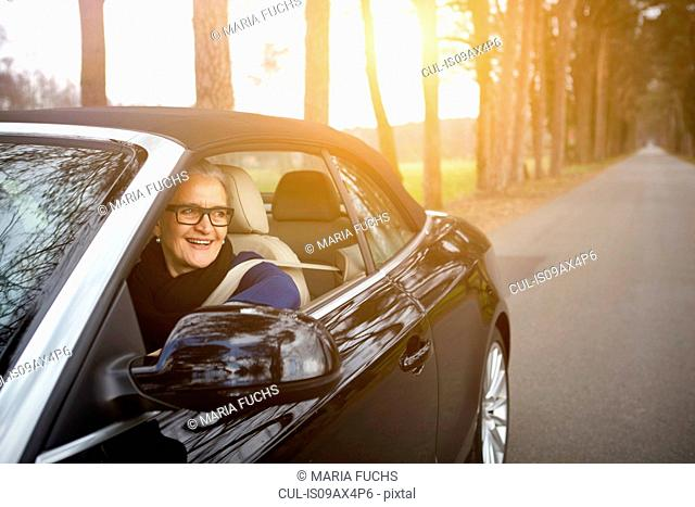 Woman in car driving on tree lined road looking out of window smiling