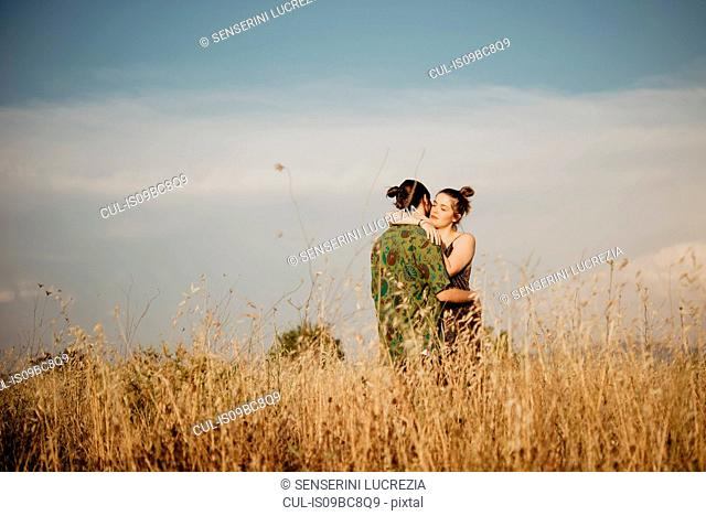 Couple on golden grass field, Arezzo, Tuscany, Italy