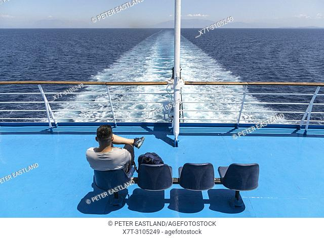 passenger on the stern of a Greek ferry watching the wake of the ship and the receding land