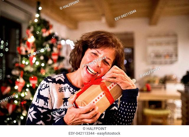 Senior woman standing in front of illuminated Christmas tree inside his house holding a present, laughing