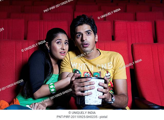 Couple watching a horror movie in a cinema hall