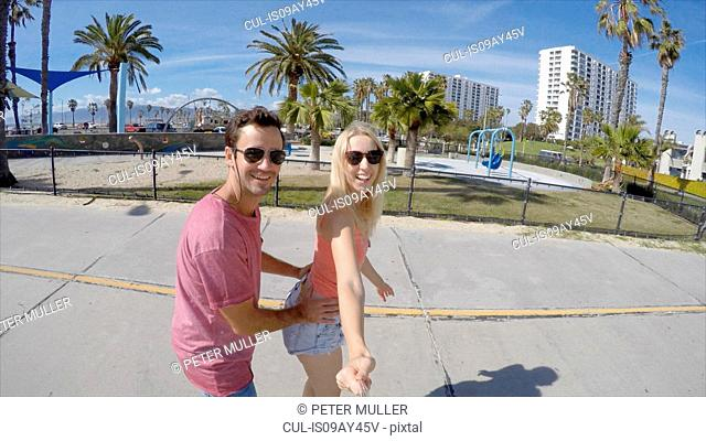 Rollerblading couple taking selfie, Venice Beach, California, USA