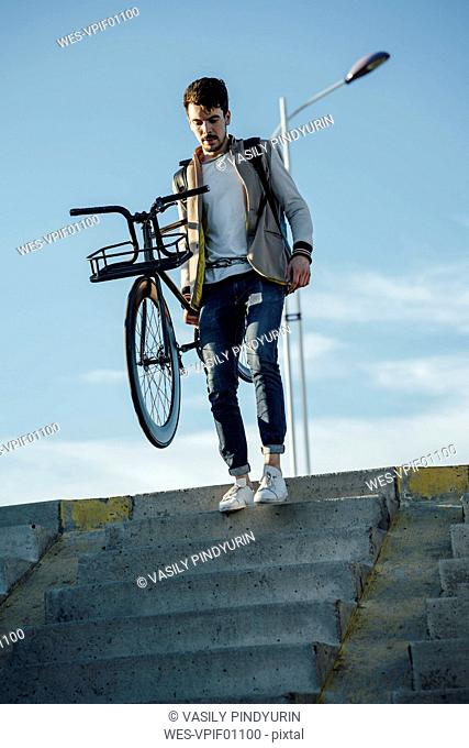 Young man carrying commuter fixie bike walking down stairs