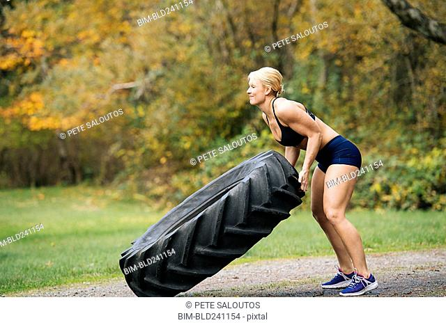 Caucasian woman lifting heavy tire in park