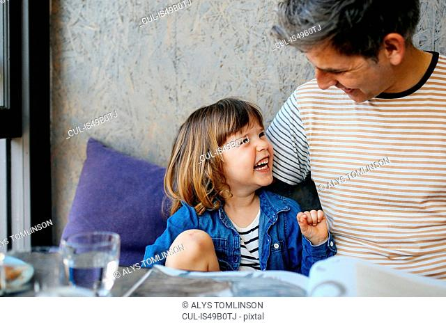 Girl laughing with father in cafe