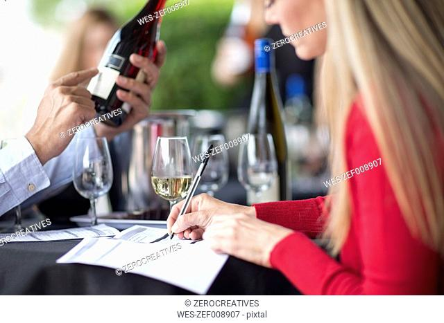 Man and woman tasting wine and taking notes