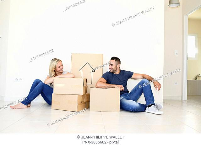 Happy young couple carrying cardboard boxes and moving into their new house