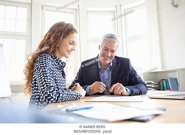 Businessman and woman at desk discussing plans