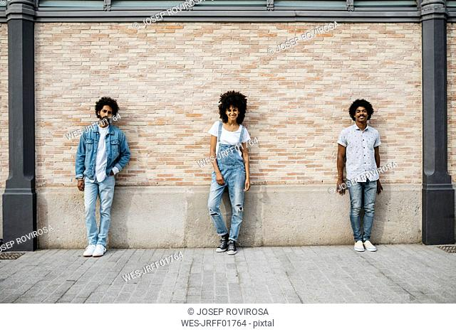 Three friends standing in front of brick wall