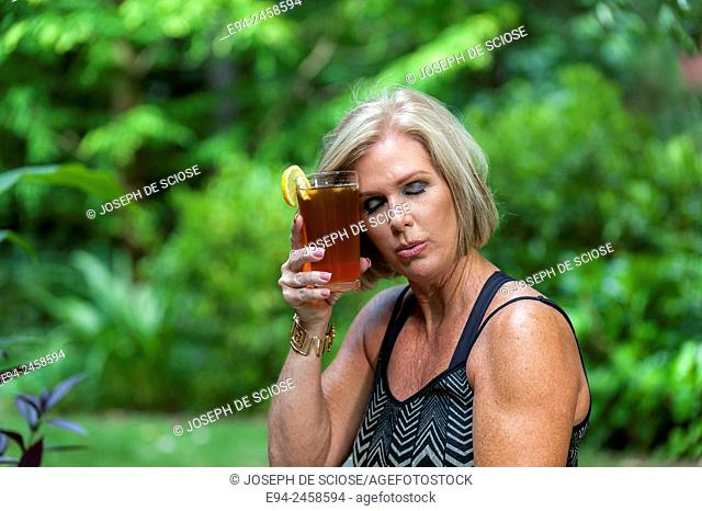 A 56 year old blond woman holding a glass of iced tea holding it to her forehead with her eyes closed