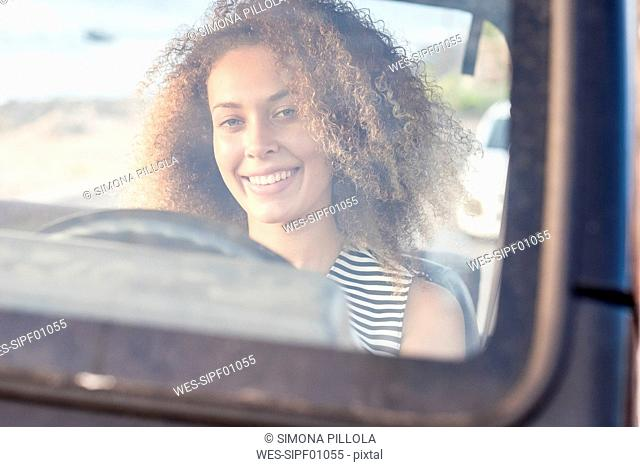 Portrait of smiling young woman sitting behind windscreen in a car