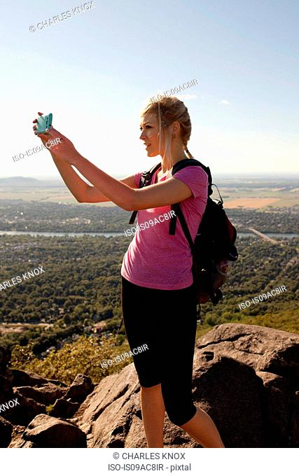 Woman on top of Mont St-Hilaire taking photograph using smartphone