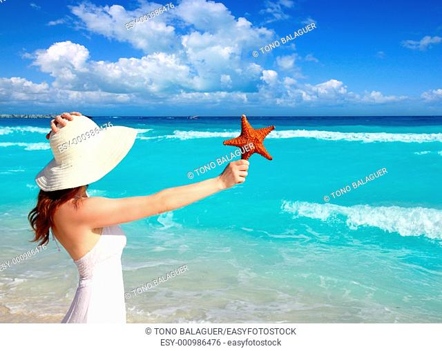 beach hat woman starfish in hand tropical turquoise Caribbean