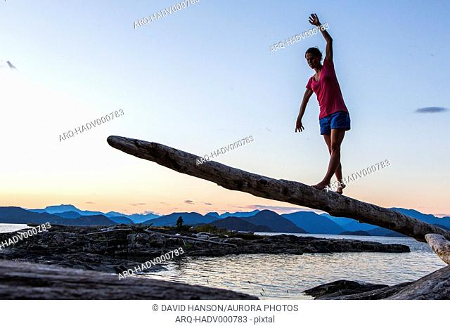 A young woman balances on a long, thin log with a background of Pacific Northwest ocean and mountains in background