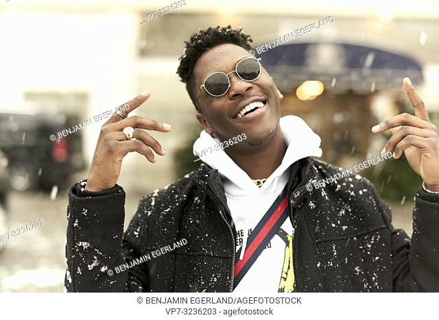 eased young man dancing in winter, snowing, in Munich, Germany